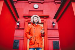Handsome young male student with toothy smile and beard stands on red wall background in bright red winter jacket with hood with f. Ur, Uses, holds mobile phone Stock Image