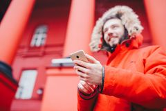 Handsome young male student with toothy smile and beard stands on red wall background, facade of educational institution in red wi. Nter jacket with hood with Stock Photography