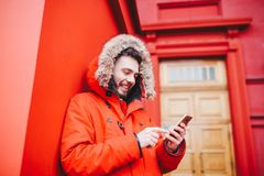 Handsome young male student with toothy smile and beard stands on red wall background, facade of educational institution in red wi. Nter jacket with hood with Royalty Free Stock Images