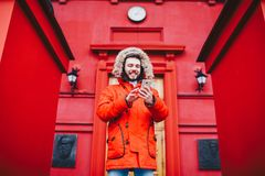 Handsome young male student with toothy smile and beard stands on red wall background, facade of educational institution in red wi. Nter jacket with hood with Stock Images