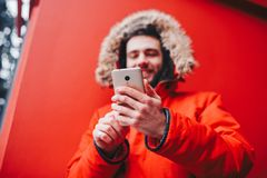 Handsome young male student with toothy smile and beard stands on red wall background, facade of educational institution in red wi. Nter jacket with hood with Royalty Free Stock Photo