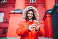 Handsome young male student with toothy smile and beard stands on red wall background, facade of educational institution in red wi. Nter jacket with hood with Stock Photo
