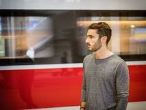 Handsome young male traveler in train station. With moving train behind him, looking to a side Stock Photo