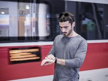 Handsome young male traveler in train station. With moving train behind him, looking at wrist watch, checking the time Royalty Free Stock Photo