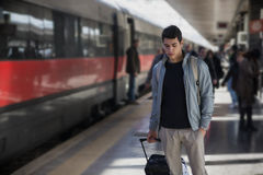 Handsome young male traveler in train station. With trolley suitcase, looking down Royalty Free Stock Photos