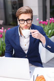 Handsome young male worker is resting in cafe. Smart businessman is relaxing in restaurant outdoors. He is sitting at table near flowers. The man is using a Stock Photos