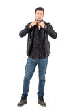 Handsome young man adjusting collar of black leather jacket looking at camera. Royalty Free Stock Image
