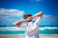 Handsome young man  against bright beach Stock Photography