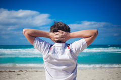 Handsome young man  against bright beach Royalty Free Stock Images
