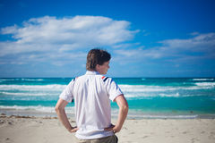Handsome young man  against bright beach Stock Photos