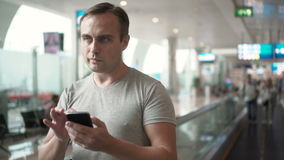 Handsome young man in airport terminal. Using travolator, looking around. Using smartphone, browsing stock video