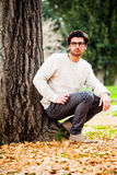 Handsome young man alone in nature near a tree outdoors Stock Images