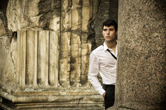Handsome young man between ancient marble columns Stock Image