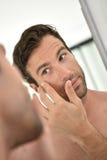 Handsome young man applying facial cream Stock Photo