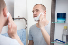 Handsome young man applying shaving cream to his face Royalty Free Stock Photos
