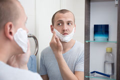 Handsome young man applying shaving foam to his face Stock Images