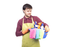 Handsome young man with apron holding cleaning equipment ready t Stock Photos