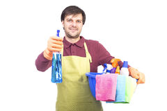 Handsome young man with apron holding a spray ready to clean the Stock Images