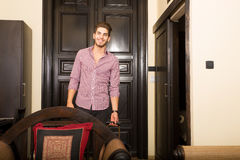 Handsome young man arriving to a hotel. A young and happy man arriving to a hotel room Stock Photos