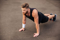 Handsome young man athlete training and doing plank exercise outdoors Stock Photos
