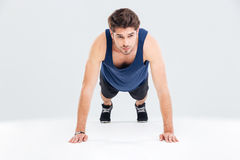 Handsome young man athlete training and doing plank exercise Stock Images