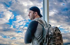 Waiting for a plane at the airport. A handsome young man with a back pack is waiting for a plane at the airport and looking out the window at a beautiful sky royalty free stock photos
