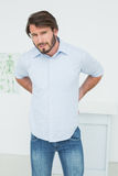 Handsome young man with back pain Royalty Free Stock Image