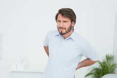 Handsome young man with back pain Stock Photography