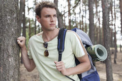 Handsome young man with backpack hiking in forest Stock Images