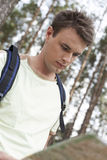 Handsome young man with backpack reading map in forest Royalty Free Stock Photos
