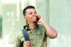 Handsome young man with backpack talking on mobile phone. Close up portrait of handsome young man with backpack talking on mobile phone Stock Image