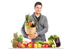Handsome young man with a bag of groceries standing behind a pil Stock Images