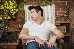 Handsome young man in balcony sleeping on chair Stock Photos
