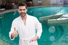 Handsome young man in bathrobe showing thumb up and smiling at camera. In spa center Stock Image