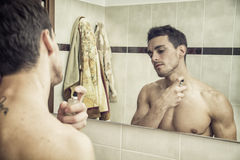 Handsome young man in bathroom, spraying cologne Stock Photo