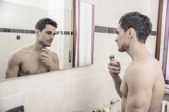 Handsome young man in bathroom, spraying cologne Royalty Free Stock Photos