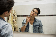 Handsome young man in bathroom, spraying cologne or perfume Stock Photos