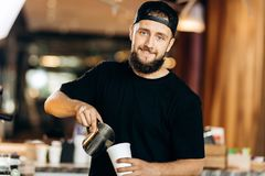 A handsome young man with beard,dressed in casual style,adds milk to the coffee in a modern coffee shop. royalty free stock photography