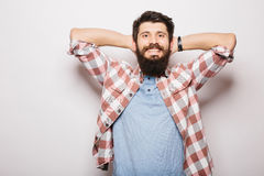 Handsome young man with beard holding hands behind head and smiling Royalty Free Stock Photos