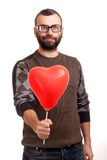 Handsome young man with beard holding red balloon Stock Photography