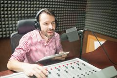 Radio jockey hosting show live on radio. Handsome young man with beard hosting show live on radio station Stock Image