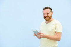 A handsome young man with a beard, looking something on a tablet close-up for your text. Royalty Free Stock Photography