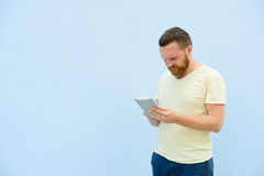 A handsome young man with a beard, looking something on a tablet close-up for your text. Royalty Free Stock Photos