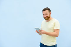 A handsome young man with a beard, looking something on a tablet close-up for your text. Stock Photography