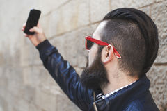 Handsome young man with a beard. Makes selfie stock images