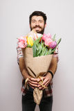 Handsome young man with beard  pointed on camera nice bouquet of flowers Stock Images