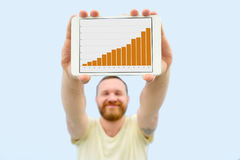 Handsome young man with a beard showing a chart on a tablet  on a blue background, close-up for your text Royalty Free Stock Photo