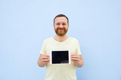 Handsome young man with a beard showing something on a tablet  on a blue background, bright and light Royalty Free Stock Images