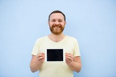 Handsome young man with a beard showing something on a tablet  on a blue background, bright and light Royalty Free Stock Image