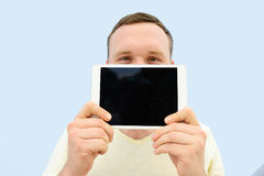 Handsome young man with a beard showing something on the tablet closing the face floor,  on a blue background, close-up fo Stock Photo